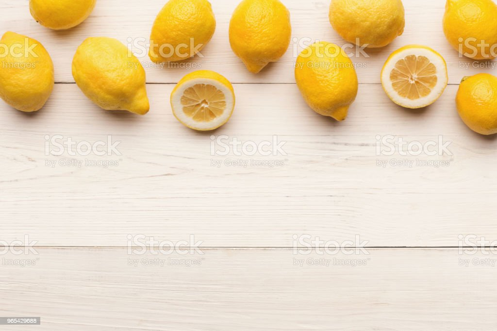 Border of lemons on white wooden planks, top view royalty-free stock photo