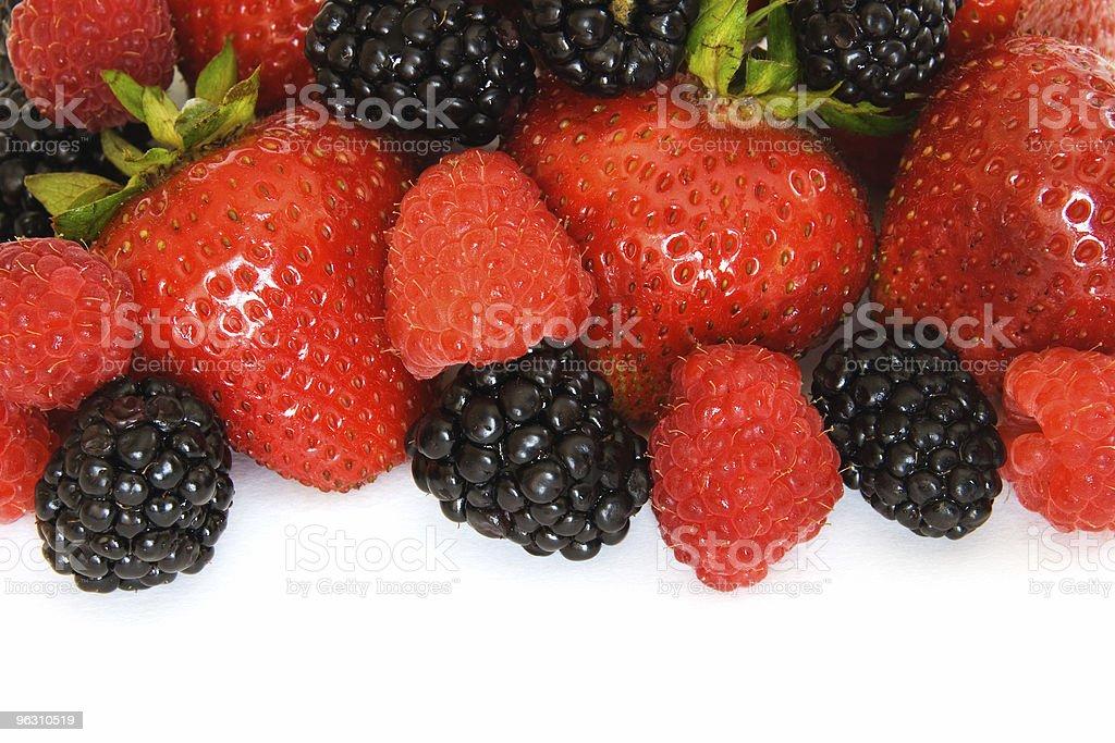 Border of mixed berries: strawberries, raspberries, and  blackberries on white royalty-free stock photo