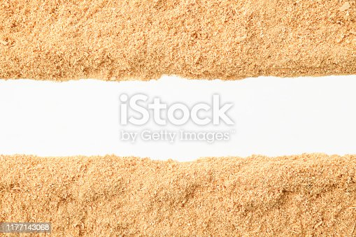 Overhead shot of border of sawdust on white background.