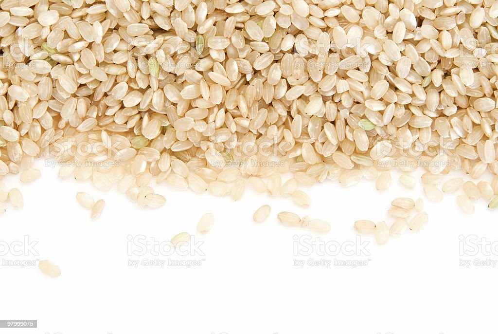 Border of short grain brown rice on white royalty-free stock photo