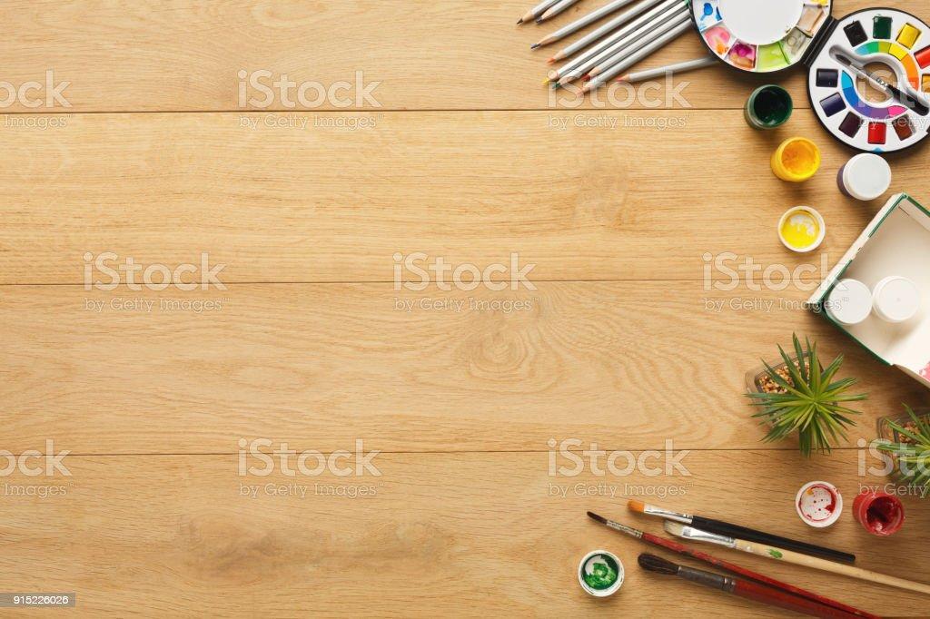 Border of various stationery for art, top view. Light wooden desktop...