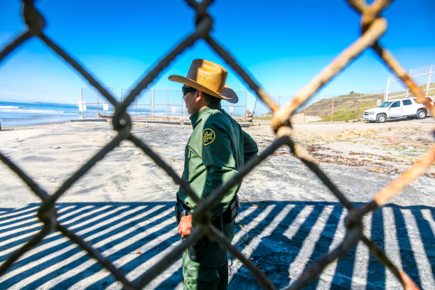 A US border officer inspects the area of the wall on the US-Mexico border Tijuana, Mexico, Feb 14 - An agent of the US Border Patrol inspects the steel wall on the border between the United States and Mexico build on the Pacific coast of Tijuana. In the background the Imperial Beach in US territory. frontier field stock pictures, royalty-free photos & images