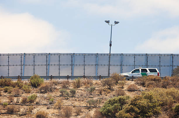 Border Partol driving along the US Mexico border San Diego, California, USA - July 4, 2016: International Border fence between USA -San Diego, and Mexico - Tijuana,  with border patrol car driving along the road. border patrol stock pictures, royalty-free photos & images