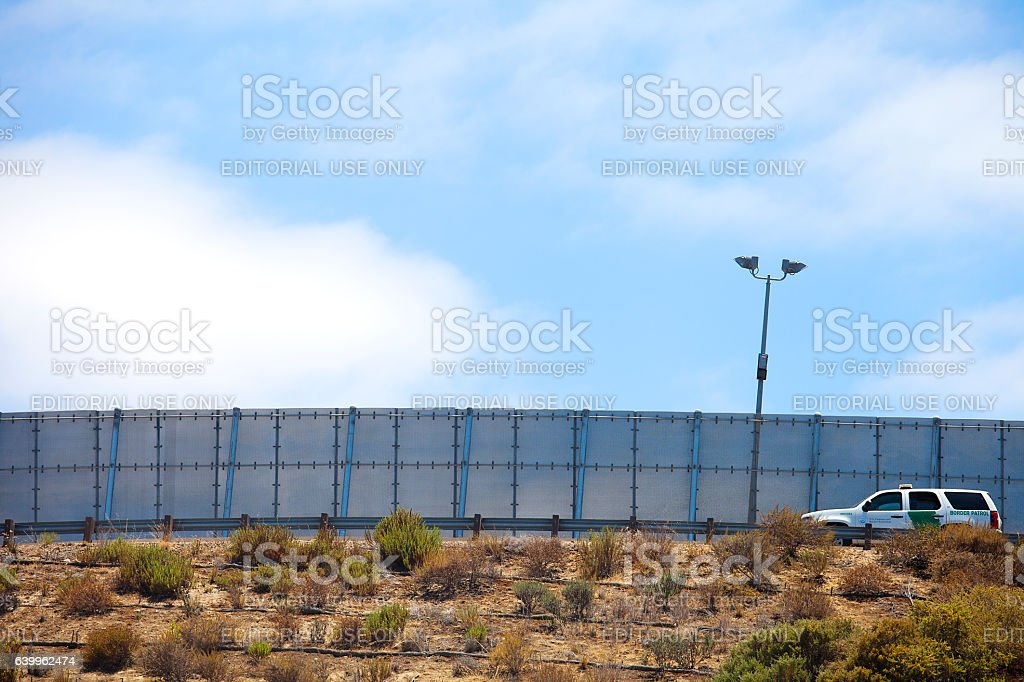 Border Partol driving along the US Mexico border wall stock photo