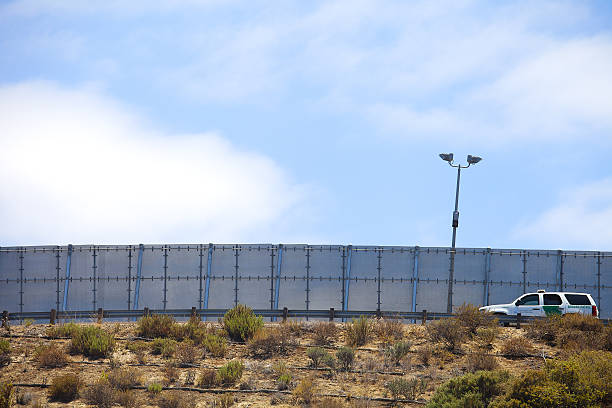 Border Partol driving along the US Mexico border wall San Diego, California, USA - July 4, 2016: International Border wall between USA -San Diego, and Mexico - Tijuana,  with border patrol car driving along the road. international border barrier stock pictures, royalty-free photos & images