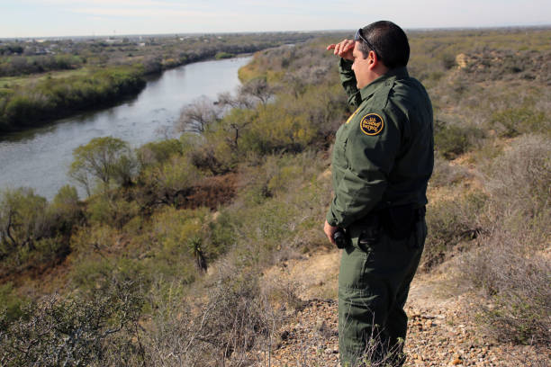Border Patrol, Rio Grande Valley Rio Grande City, Texas, USA - January 30, 2018: A Border Patrol agent shields his eyes from the late morning sun as he looks at Mexico across the Rio Grande River in deep south Texas. This stretch of the river has recently seen an upsurge in crossings, both of people and marijuana. border patrol stock pictures, royalty-free photos & images