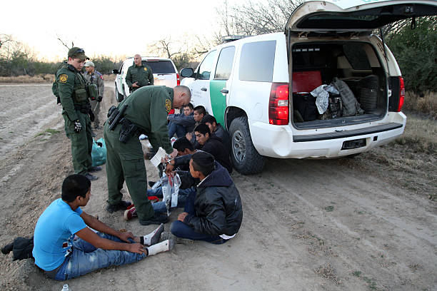 Border Patrol, Rio Grande Valley, Texas, Feb. 9, 2016 Fronton, Texas, USA - February 9, 2016: A Border Patrol agent removes handcuffs from a young Central American being taken into custody for illegally entering the United States by crossing the Rio Grande River in deep south Texas. Young Central Americans, most fleeing gang violence and poverty, continue to illegally enter the U.S. at near record levels. border patrol stock pictures, royalty-free photos & images