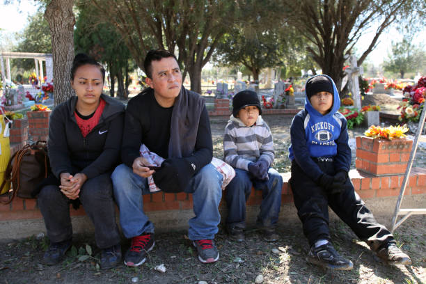 Border Patrol, Rio Grande Valley, Texas, Feb. 9, 2016 Roma, Texas, USA - February 9, 2016: A family from El Salvador waits to be taken into custody at the city cemetery after being detained by the Border Patrol for illegally entering the United States by crossing the Rio Grande River. The family, from San Vicente, was fleeing gang violence, which is rampant in El Salvador. central america stock pictures, royalty-free photos & images