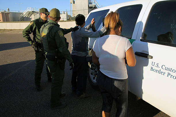 Border Patrol, Rio Grande Valley, Texas, Feb. 9, 2016 Rio Grande City, Texas, USA - February 9, 2016: Two Border Patrol agents take a Mexican man into custody for illegally entering the U.S. by crossing the Rio Grande River in the Rio Grande Valley in far south Texas. A continuous game of cat and mouse plays out along the river twenty four hours a day. department of homeland security stock pictures, royalty-free photos & images