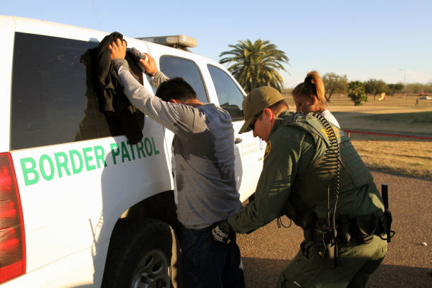 Border Patrol, Rio Grande Valley, Texas, Feb. 9, 2016 Rio Grande City, Texas, USA - February 9, 2016: A Border Patrol agent takes a Mexican man into custody for illegally entering the U.S. by crossing the Rio Grande River in the Rio Grande Valley in far south Texas. A continuous game of cat and mouse plays out along the river twenty four hours a day. geographical border stock pictures, royalty-free photos & images