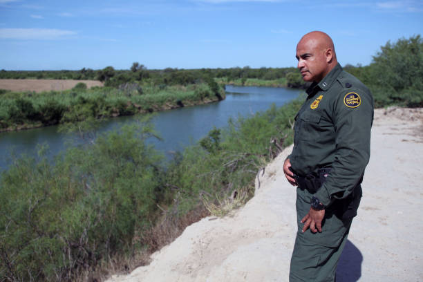 Border Patrol, Rio Grande Valley, Texas, Sept. 21, 2015 Roma, Texas, USA - September 21, 2015:  A Border Patrol agent looks across the Rio Grande River towards the Mexican town of Miguel Aleman.  This stretch of the river is notorious for being used to ship drugs, primarily marijuana, to the United States. border patrol stock pictures, royalty-free photos & images