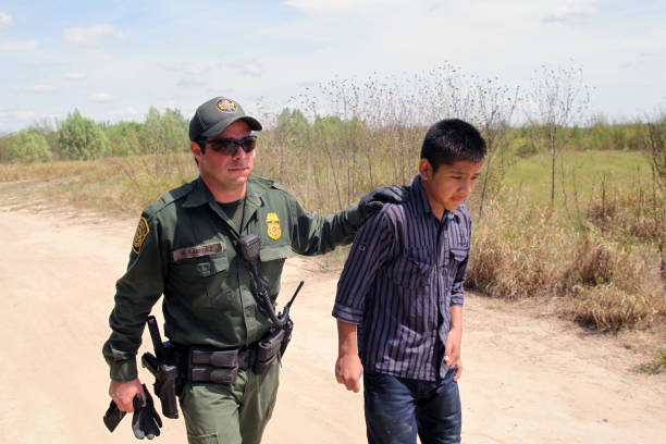 Border Patrol, Rio Grande Valley, Texas, Sept. 21, 2015 La Grulla, Texas, USA - September 21, 2015: A  Border Patrol agent takes a 14 year old Honduran boy into custody after apprehending him on the banks of the Rio Grande River attempting to enter the United States illegally.  There was a sharp increase in the number of unaccompanied Central American juveniles, most fleeing gang violence, trying to enter the U.S. illegally over the summer. department of homeland security stock pictures, royalty-free photos & images