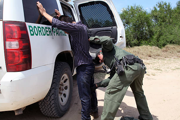 Border Patrol, Rio Grande Valley, Texas, Sept. 21, 2015 La Grulla, Texas, USA - September 21, 2015: A  Border Patrol agent searches a 14 year old Honduran boy he apprehended on the banks of the Rio Grande River attempting to enter the United States illegally.  There was a sharp increase in the number of unaccompanied Central American juveniles, most fleeing gang violence, trying to enter the U.S. illegally over the summer. department of homeland security stock pictures, royalty-free photos & images