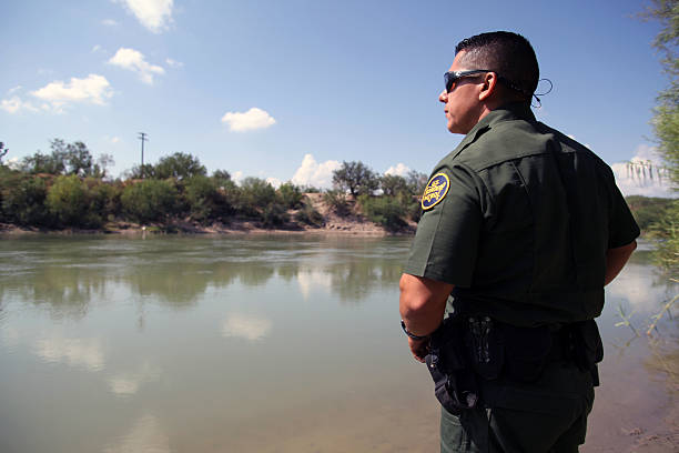 Border Patrol, Rio Grande Valley, Texas, Sept. 21, 2016 McAllen, Texas, USA - September 21, 2016:  A Border Patrol agent looks at Mexico across the Rio Grande River in deep south Texas. There has been a flood of mothers with children and unaccompanied minors from Central America fleeing gang violence crossing illegally over the past several months. department of homeland security stock pictures, royalty-free photos & images