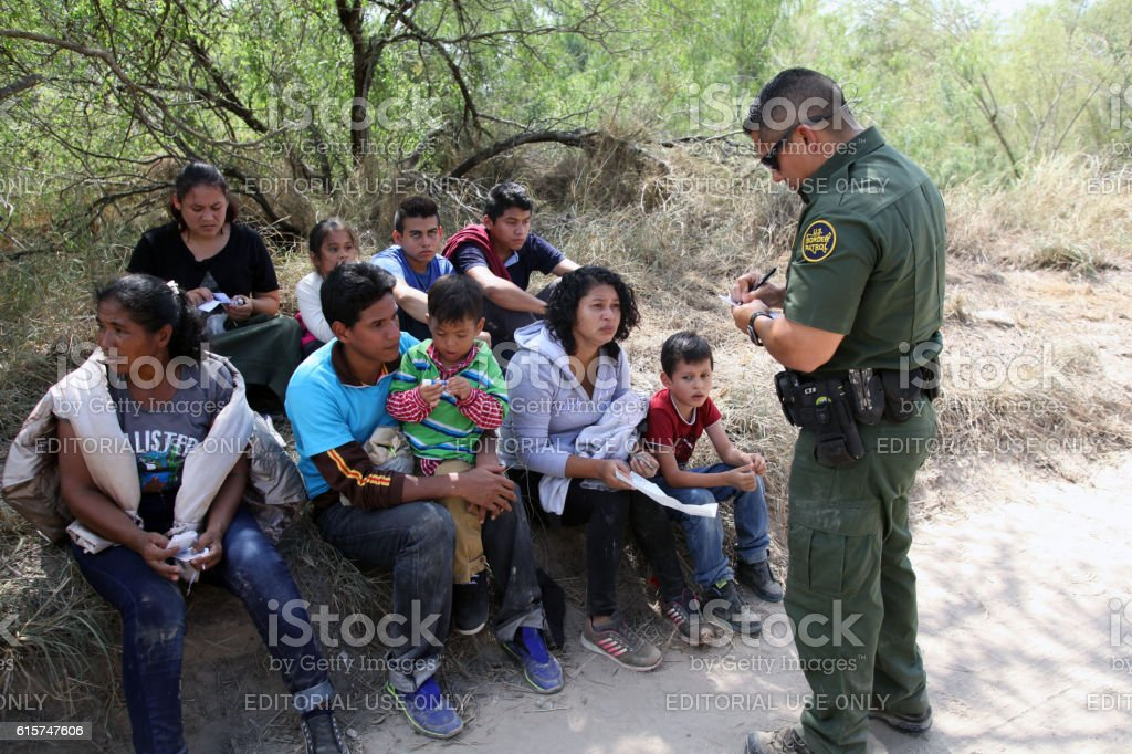 Border Patrol, Rio Grande Valley, Texas, Sept. 21, 2016 McAllen, Texas, USA - September 21, 2016: A Border Patrol agent takes a group of Central Americans into custody for illegally crossing the Rio Grande River into the U.S. in deep south Texas. There has been a flood of mothers with children and unaccompanied minors from Central America fleeing gang violence crossing illegally over the past several months. Border Patrol Stock Photo