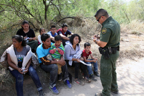 Border Patrol, Rio Grande Valley, Texas, Sept. 21, 2016 McAllen, Texas, USA - September 21, 2016: A Border Patrol agent takes a group of Central Americans into custody for illegally crossing the Rio Grande River into the U.S. in deep south Texas. There has been a flood of mothers with children and unaccompanied minors from Central America fleeing gang violence crossing illegally over the past several months. border patrol stock pictures, royalty-free photos & images