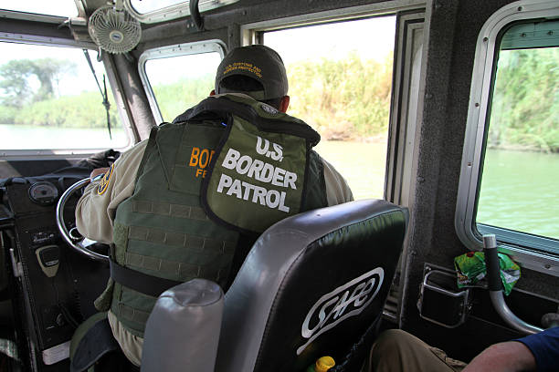 Border Patrol, Rio Grande Valley, Texas, Sept. 22, 2015 La Paloma, Texas, USA - September 22, 2015:  A Border Patrol agent pilots a river patrol boat and monitors the Rio Grande River for illegal aliens crossing into the U.S.  Such encounters are a daily experience in the Rio Grande Valley sector of Border Patrol operations. department of homeland security stock pictures, royalty-free photos & images