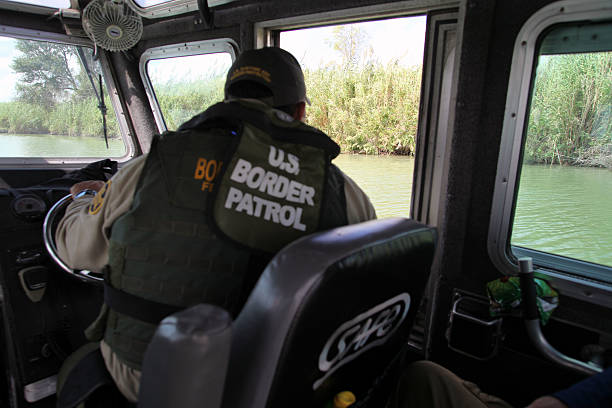 Border Patrol, Rio Grande Valley, Texas, Sept. 22, 2015 La Paloma, Texas, USA - September 22, 2015:  A Border Patrol agent pilots a river patrol boat and monitors the Rio Grande River for illegal aliens crossing into the U.S.  Such encounters are a daily experience in the Rio Grande Valley sector of Border Patrol operations. border patrol stock pictures, royalty-free photos & images