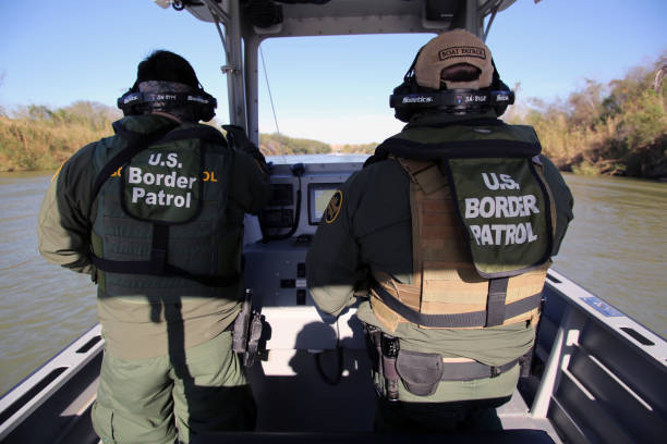 Border Patrol Riverine, Rio Grande River McAllen, Texas, USA - January 29, 2018: Two Border Patrol agents on a small river patrol boat monitor the Rio Grande River for illegal aliens crossing into the U.S. Such encounters are a daily experience in the Rio Grande Valley sector of Border Patrol operations. border patrol stock pictures, royalty-free photos & images