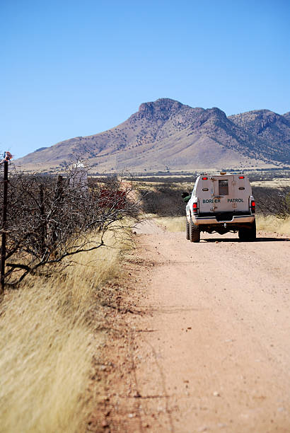 Border patrol truck driving to mountains Border patrol vehicle on a dirt road along the Mexican border, driving towards Coronado in Arizona border patrol stock pictures, royalty-free photos & images
