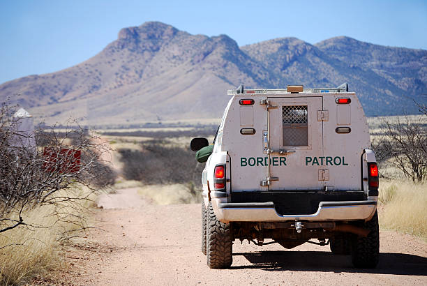 Border patrol truck with Arizona mountains Back of a border patrol truck driving on a dirt road along the Mexican border in Arizona, with mountains in the background department of homeland security stock pictures, royalty-free photos & images