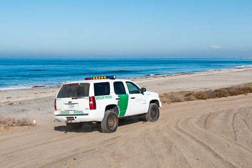 San Diego, California - November 4, 2017:  A Border Patrol vehicle patrols the beach at Border Field State Park, the southwesternmost beach in the USA, across the border wall from Tijuana, Mexico.
