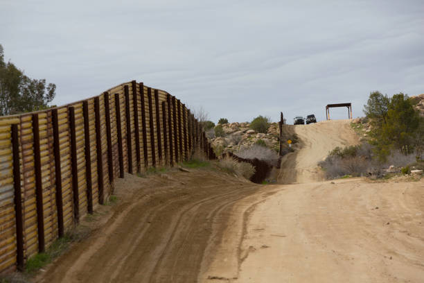 Border Patrol Vehicles Near Barrier Wall in California Border Patrol Vehicles near wall  seperating the United States from Mexico geographical border stock pictures, royalty-free photos & images