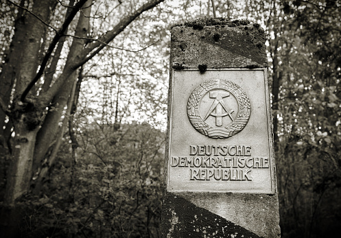 Braunlage, Germany - April 29, 2018: Border pillar of the former inner German border with the emblem of the GDR in the forest in the Harz National Park in Germany