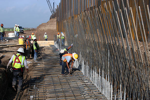 Border Wall, Rio Grande Valley, Texas, Aug., 2008 Granjeno, Texas, USA - August 15, 2008:  Construction workers erect a border wall ordered by the Department of Homeland Security to deter illegal immigrants from entering the U.S. just north of the Rio Grande River in the Rio Grande Valley in deep south Texas.  The effectiveness of the wall is a matter of dispute, as immigrants continue to enter illegally on a daily basis. international border barrier stock pictures, royalty-free photos & images