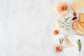 istock Border with a selection of cheeses, figs, nuts and crackers on a white marble background with copy space 1180275032