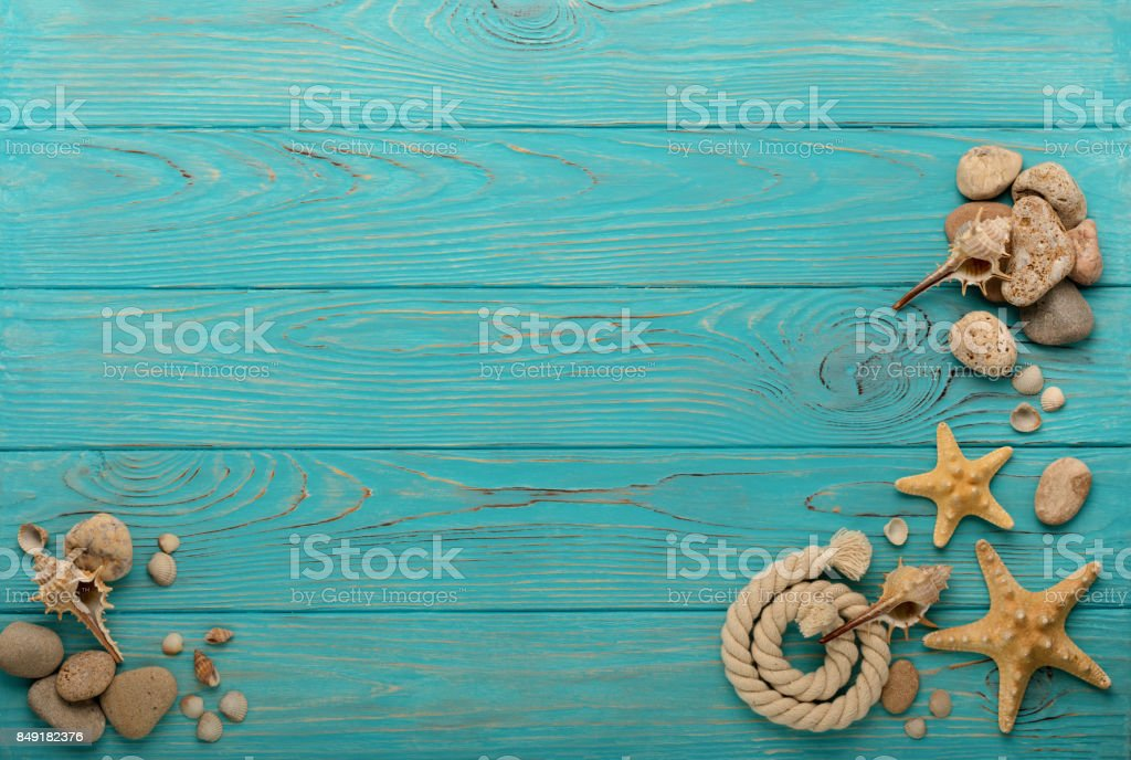 Border with rope, stones, sea shells and starfish on a turquoise wooden background. stock photo