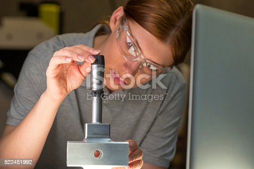 Female using a bore micrometer to measure . The woman is wearing safety goggles. Close up