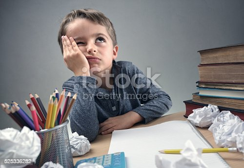 istock Bored and fed boy up doing his homework 525336282