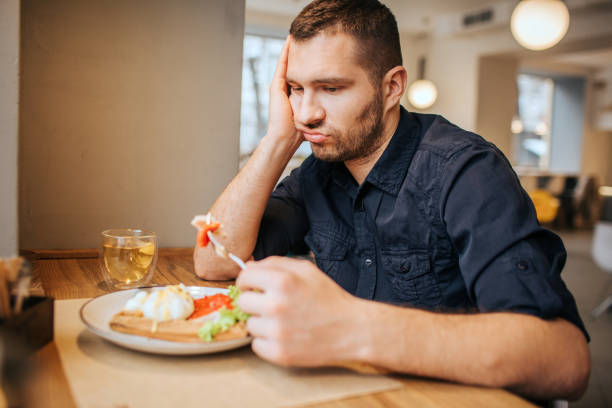 bored and sad man is sitting at table and cafe. he is holding a piece of vegetable on fork. man is looking at it and breathing out - slow food foto e immagini stock