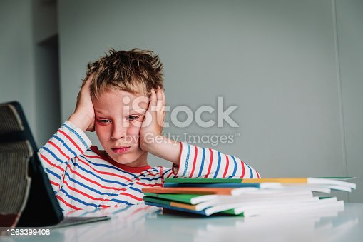 Bored and sad teenager looking at computer, kid tired of online communication and learning, boy exchaused by remote education
