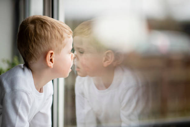 Bored at Home A shot of a young caucasian boy looking out of the window. boy looking out window stock pictures, royalty-free photos & images