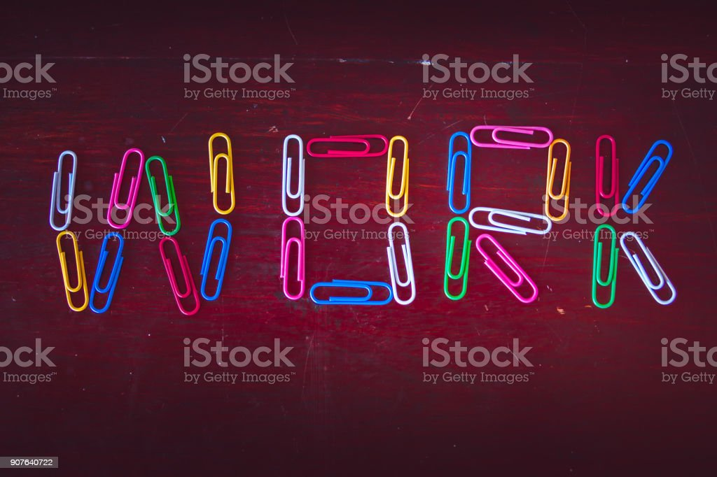 Bored at the Office knolling concept: Single word 'work' made with paper clips on desk stock photo