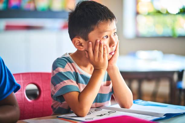 Bored boy looking away at classroom stock photo