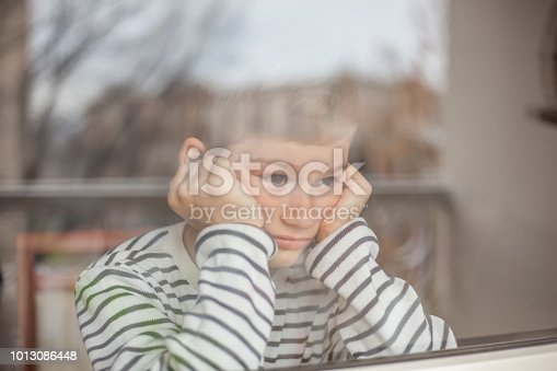 Portrait of an unhappy-looking little boy sitting and looking out a window