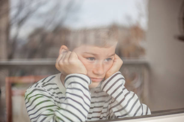 bored boy looking through window - boy looking out window stock pictures, royalty-free photos & images