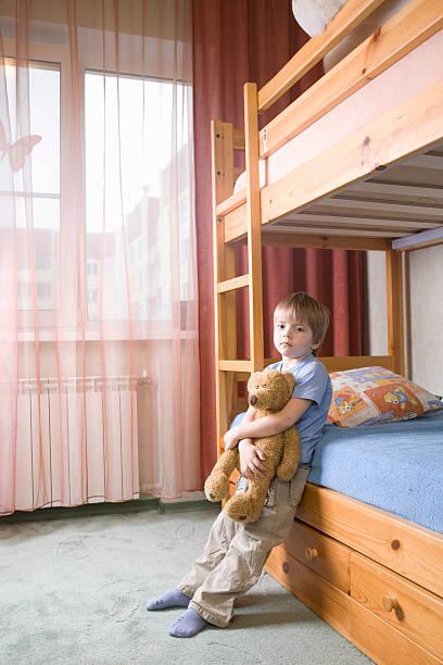 gelangweilt junge mit teddy bear lehnend auf etagenbett - etagenbett weiss stock-fotos und bilder