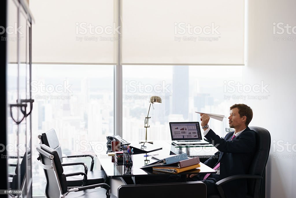 Bored Business Man Throwing Paper Airplane In Office stock photo