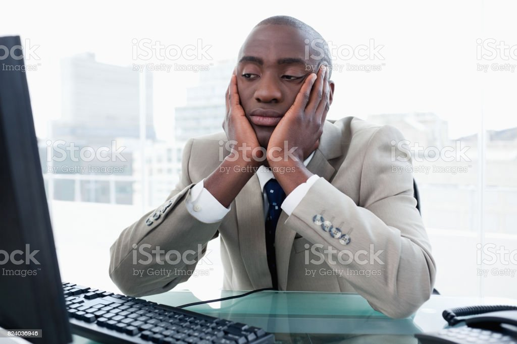 Bored businessman looking at his computer stock photo