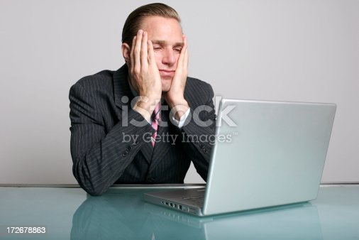 istock Bored Businessman Looking Tired of Waiting at Desk Laptop 172678863