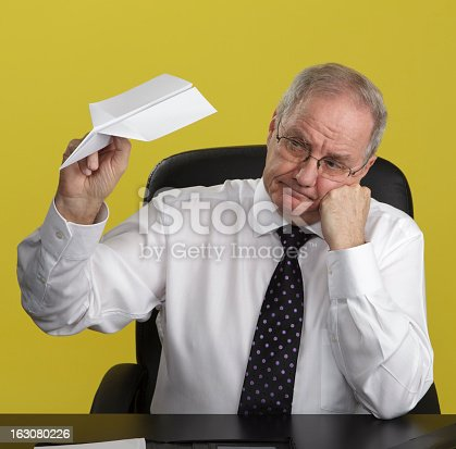 A bored-looking businessman sitting at his desk with no work to do, playing with a paper aeroplane. Yellow background.