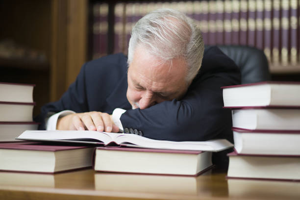 Bored businessman sleeping on books in his office stock photo
