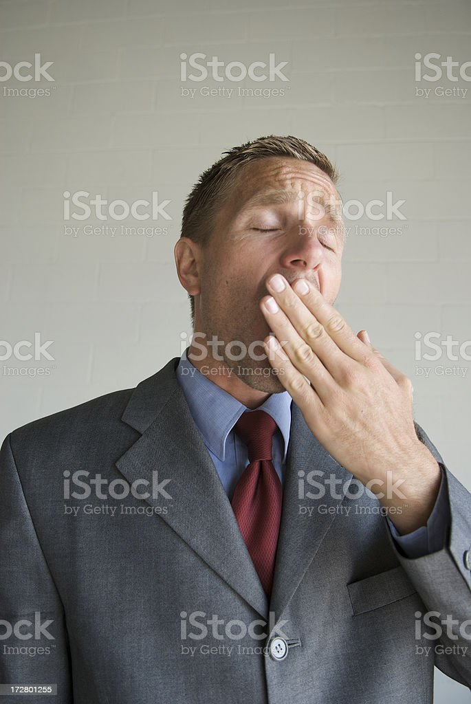 Bored Businessman Stifling a Yawn with Hand over Mouth royalty-free stock photo