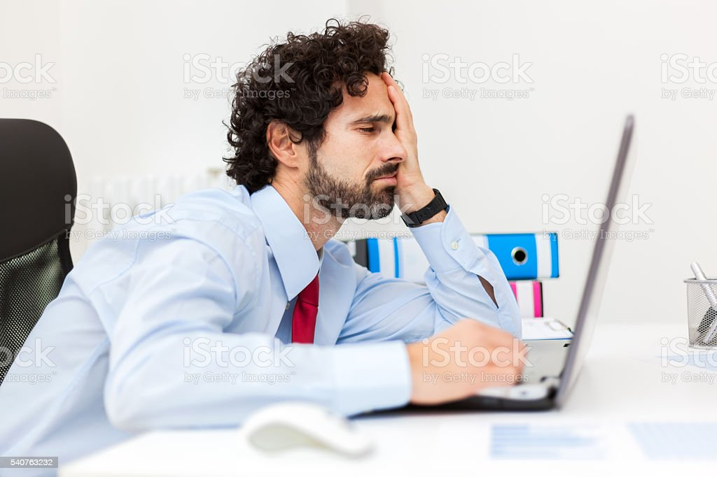 Bored businessman working at his laptop - Foto de stock de Aburrimiento libre de derechos
