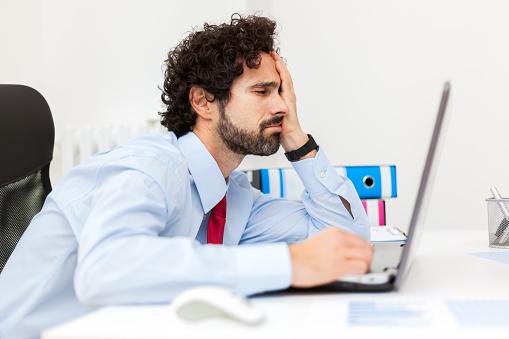 Bored Businessman Working At His Laptop Foto de stock y más banco de imágenes de Aburrimiento