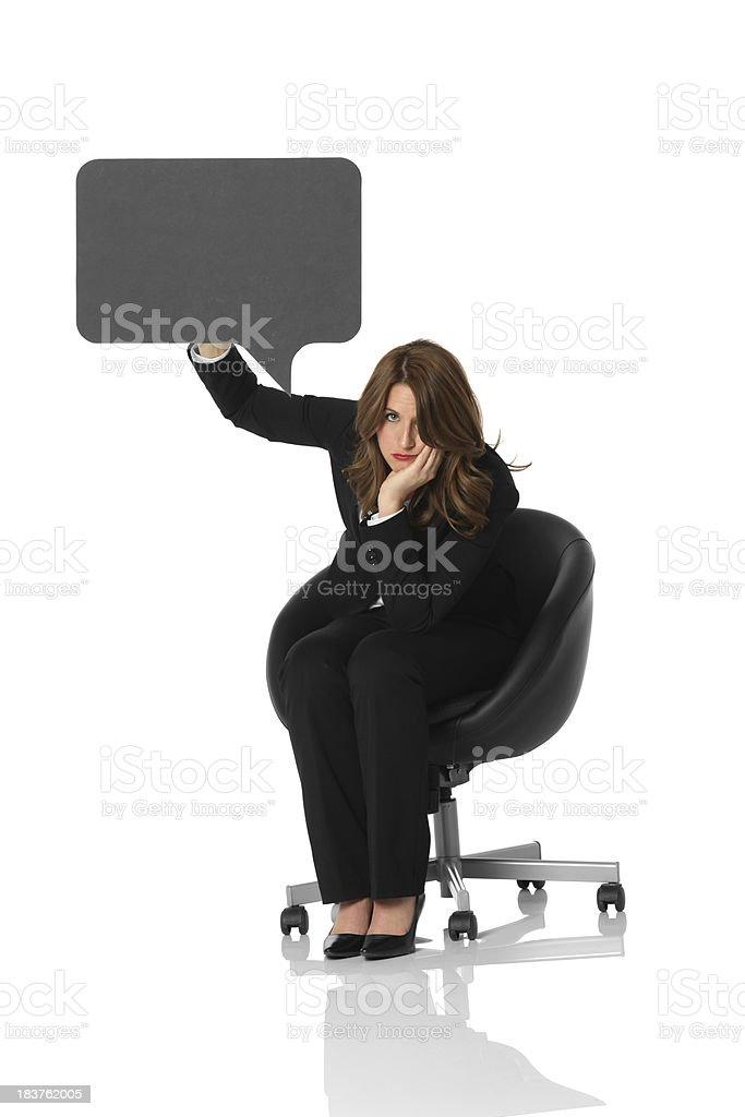 Bored businesswoman sitting with speech bubble stock photo